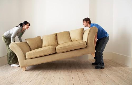 Couple qui soulève un canapé pendant un déménagement
